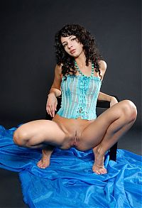 Nake.Me search results: cute young curly brunette girl undresses her blue corset on the table