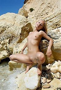 Babes: cute young blonde girl reveals on the rocky coast at the sea