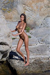 Babes: young brunette girl in the sea on the rocky coast