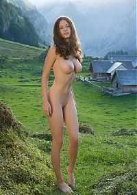 Nake.Me search results: young curly brunette girl shows off in the alpine mountains above the valley tarn and a small village
