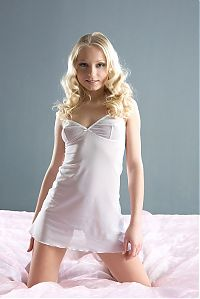 Nake.Me search results: young blonde girl on pink bed sheets reveals in a white negligee