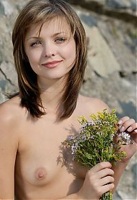 Babes: cute young dark blonde girl reveals outside in the nature on rocks
