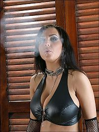 Babes: brunette girl smoking a cigarette in a latex bondage clothing