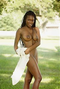 Babes: black girl with long hair reveals outside on the green grass