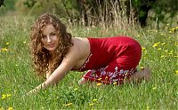 Babes: young curly brunette girl strips her red dress on the field of wild flowers