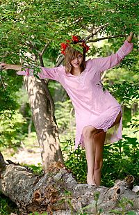 Nake.Me search results: young dark blonde girl with blue eyes and a floral wreath reveals a pink nightgown in the forest