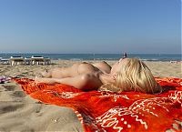 Nake.Me search results: young blonde girl with a tattoo undresses her bikini on the beach towel at the sea