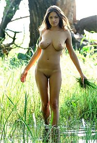 Babes: cute young brunette girl with full breasts in the swamp at the big tree