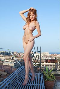 Babes: red haired girl on the roof terrace with the rattan deckchair and flowers