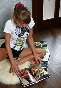Nake.Me search results: young blonde girl strips on the floor with a fur and looks through nude photo-books