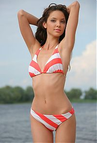 Nake.Me search results: young curly brunette girl undresses a red white bikini on the bank of the lake