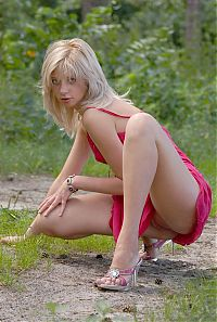 Nake.Me search results: cute young blonde girl reveals her pink chemise on the forest pathway with tree trunk