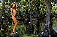Nake.Me search results: young brunette girl with a fishing net reveals in the swampland with trees