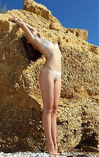 Nake.Me search results: young blonde girl with blue eyes takes off her bra near sedimentary rocks at the sea coast