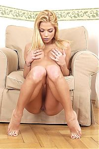 Babes: blonde girl undresses her black bra, panties, hold-ups and high heels on the sofa chair