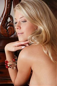 Babes: cute young blonde girl with blue eyes reveals her body with earrings and bracelets near the vanity table with the mirror