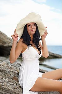 Nake.Me search results: black haired girl with a hat reveals her white dress on the rocky shore at the sea