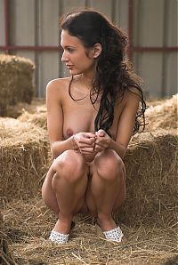 Nake.Me search results: young curly brunette girl with a navel piercing posing in the barn with a hay