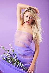 Nake.Me search results: young blonde girl with blue eyes and flowers reveals her body in blue textile fabrics in the purple studio