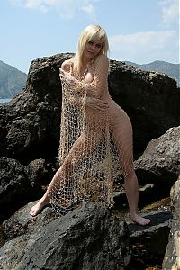 Nake.Me search results: blonde girl reveals her shell necklace and fishing net on the rocky coast at the sea