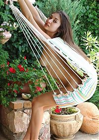 Nake.Me search results: cute young brunette girl with long hair reveals her body on the hammock sling in the backyard garden
