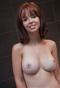 young red haired girl with big breasts shows off her body in the bathroom