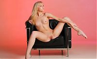 cute young blonde girl with blue eyes undresses her pink brassiere and boyshorts on the black sofa chair