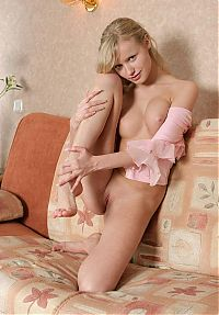 Babes: young blonde girl reveals her pink blouse top on the old couch at home