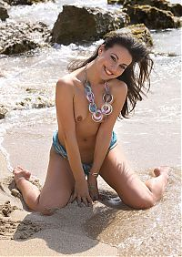 Babes: young brunette girl with a scarf, necklace, bracelet and earrings reveals on the rocky shore at the sea