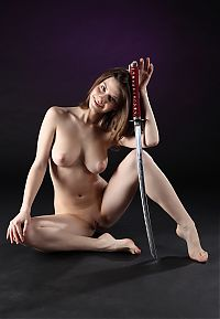 Nake.Me search results: young brunette girl reveals her full natural breasts while posing with japanese katana sword