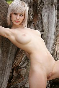 Nake.Me search results: young blonde girl with small earrings shows off her body at the old tree outside in the nature