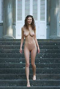 young curly brunette girl shows off outside at the entrance of the building with tall columns grid