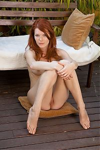Babes: young red haired girl with facial freckles undresses her white t-shirt and panties on the bench with pillows in the backyard garden