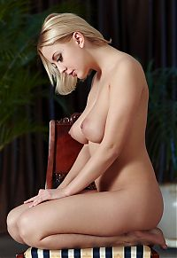 Babes: blonde girl with a mask shows off her body on the chair at home