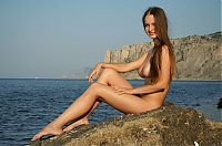 cute young brunette girl with long hair and blue eyes reveals her pubic hair landing strip and big breasts on the rocky shore at the sea