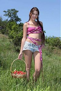 Nake.Me search results: young brunette girl with a pigtail and strawberries in the handbasket undresses her pink bra and short jeans outside on the open glade area