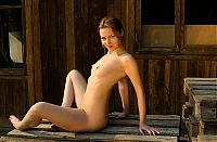 young dark blonde girl with french braid shows off her earrings, navel piercing and pubic hair landing strip with building material and bricks near the forest