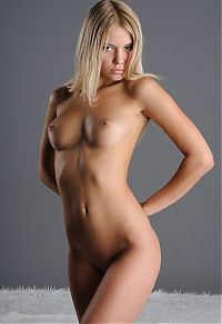 cute young blonde girl reveals naked on the white fur carpet in the grey studio