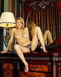 Babes: young golden blonde girl with earrings reveals her high heels and black thongs at the vanity table with lamp and mirror, antique chair and curtains