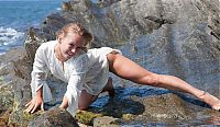 Babes: young blonde girl undresses her white blouse on the rocky shore at the sea