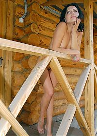 Babes: cute young black haired girl shows off on the wooden porch
