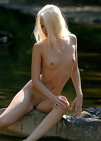 young blonde girl with green eyes posing naked at the rocky mountain stream