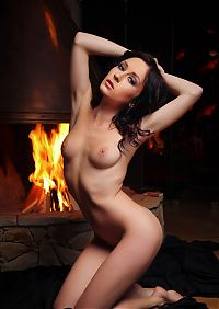 Nake.Me search results: curly brunette girl with black sheets posing in front of the fireplace