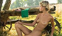 young dirty blonde girl undresses her pink panties at the old hay wagon under the tree
