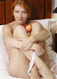 Nake.Me search results: curly red haired girl undresses her white panties and cardigan while eating an apple in the bed