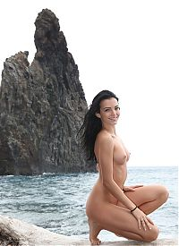 Babes: young black haired girl reveals her short jeans on the driftwood on the rocky shore at the sea