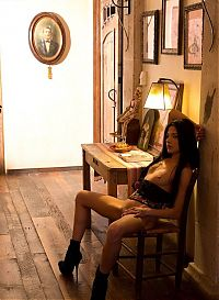 Babes: young black haired girl reveals her corset in the old wooden cottage