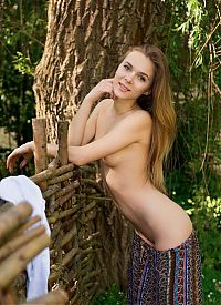 Babes: young dark blonde girl reveals her dress near the wooden fence