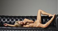 Babes: young blonde girl with a navel piercing shows off on the black leather couch