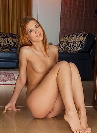 Babes: young red haired girl shows off in the living room at home